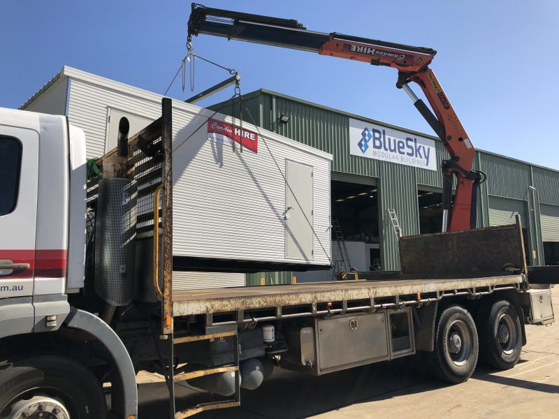 Portable building being transported